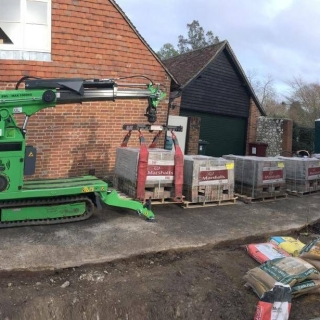 Hooka all terrain tracked forklift on hire in Midhurst West Sussex - safely lifting and moving heavy pallet of Marshalls paving blocks