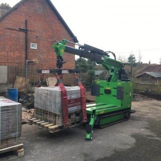 Hooka all terrain tracked forklift safely lifting and moving heavy pallet of Marshalls paving blocks
