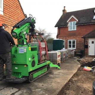 Hooka all terrain tracked mini crane on hire to safely lift and move heavy pallet of Marshalls paving slabs