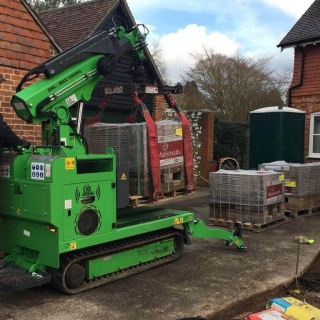 Hooka all terrain tracked powered pallet truck and mini crane on hire in West Sussex to easily lift and move heavy pallet of Marshalls paving blocks