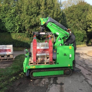 Hooka all terrain tracked powered pallet truck and mini crane on hire in West Sussex to easily lift and move heavy pallet of Marshalls paving slabs