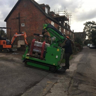 Hooka all terrain tracked powered pallet truck and mini crane on hire in West Sussex to safely lift and move heavy pallet of Marshalls paving blocks