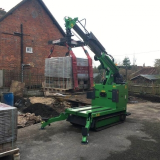Hooka all terrain tracked powered pallet truck and mini crane on hire in West Sussex to safely lift and move heavy pallet of Marshalls paving slabs