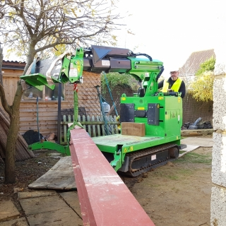 The Hooka mini tracked crawler crane on hire carrying a steel beam to the rear of a property using a dolly instead of a conventional crane hire. Hired from Hook-up Solutions call 01462 499 642