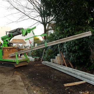 4 - The Hooka tracked forklift mini crane lifts heavy concrete beams ready to carry through site wit