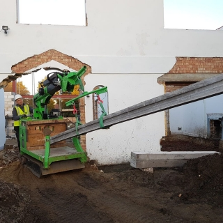 5 - The Hooka forklift mini crane transports heavy concrete beams through small opening on site with