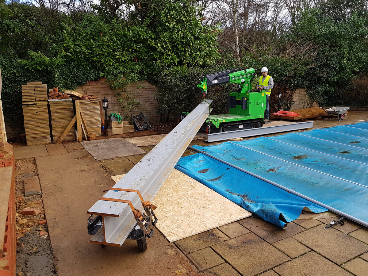 The Hooka lift carry all terrain mini crane easily and safely moving steel i-beam on site with restricted access over swimming pool
